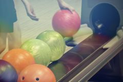 Hands of young girl picks up a bowling ball. Bowling ball on the background of the silhouette of the girl, hands of young girl picks up a bowling ball Royalty Free Stock Photos