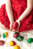 The girl`s hands hold decorated Easter eggs. Hands of a young girl in a red dress holding decorated Easter eggs Royalty Free Stock Photography