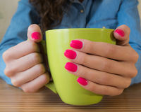 Hands of a young girl with red nail Polish holding a big green C. The girl in blue denim shirt and red nail Polish sits at a wooden table and keeps the big green Stock Photography