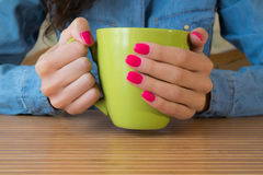 Hands of a young girl with red nail Polish holding a large green. Girl in a denim shirt and red nail Polish sits at a wooden table and keeps a big green Cup Royalty Free Stock Images