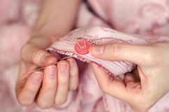 Hands of a young girl sew a button close up. Hands of a young girl sew a button with a needle close up Royalty Free Stock Photography