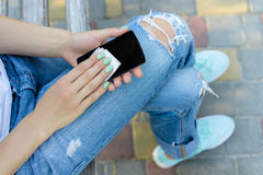 Hands of a young girl wipe mobile phone antibacterial cloth Royalty Free Stock Images