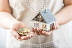 Hands of young hosewife holding model house stock photo