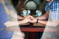 Hands of young lovers holding a hot cup coffee Stock Photo