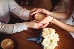 Hands of young lovers holding a hot cup  coffee. Hands of young lovers holding a hot cup of coffee with white heart shaped smoke Royalty Free Stock Photo