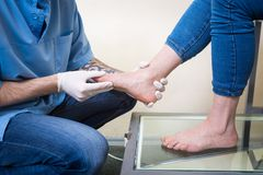 The hands of a young man doctor orthopedist conducts diagnostics, foot foot test of a woman, for the manufacture of individual, or. Thopedic insoles royalty free stock photo