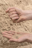Hands of a young man pour sand from one hand to another Royalty Free Stock Photos