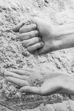 Hands of a young man pour sand from one hand to another Stock Photo