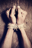 The hands of a young man tied with rope. High-angle shot of the hands of a young man tied with rope on a rustic wooden table, as a symbol of oppression or Stock Images