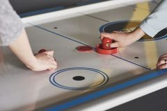 Hands of young people holding striker on air hockey table in game room.  royalty free stock photos