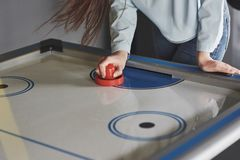Hands of young people holding striker on air hockey table in game room.  royalty free stock images
