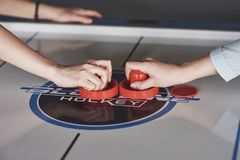 Hands of young people holding striker on air hockey table in game room.  stock photo