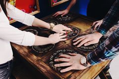 The hands of young people move pieces of the Mexican style trying to get out of the trap. Escape the room game concept stock photo