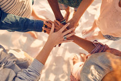 Hands of young people on stack at beach. Closeup image of hands of young people with on stack. Group of mixed race friends on the beach with their hands stacked Stock Images