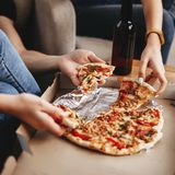 Hands of young people taking pizza slices. From delivery box dining together, millennial friends sharing meal having lunch at home, food delivery concept royalty free stock photo
