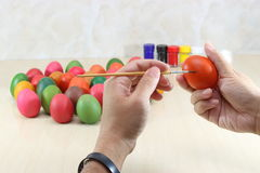 Hands of young relaxed man painting colorful eggs on marble top with copyspace background preparing easter day. Hands of young relaxed man painting colorful Royalty Free Stock Photography