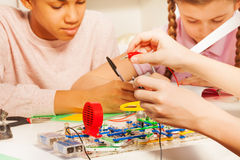 Hands of young student with potential probes. Young students measuring electrical voltage of electric chain with potential probes Stock Image