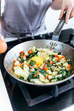 Hands of a young woman adding egg to vegetables into the pan. Royalty Free Stock Images