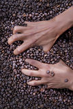 Hands of a young woman and coffee beans Royalty Free Stock Photography