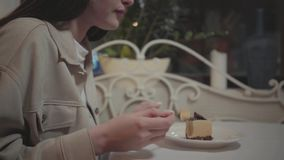 Young woman eating small piece of tasty cake close up in the cafe. The girl enjoying her dessert in the modern. The hands of the young woman eating a small piece stock video footage