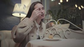 Portrait of young woman eating small piece of tasty cake close up in the cafe. The girl enjoying her dessert in the. The hands of the young woman eating a small stock footage
