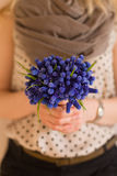 Hands of a young woman holding a bunch of beautiful spring blue flowers. Vertical stock photo