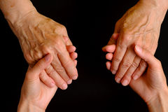 Hands of young woman holding hands of an elderly woman Stock Images