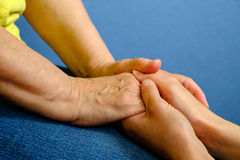 Hands of young woman holding hands of an elderly woman Royalty Free Stock Photography