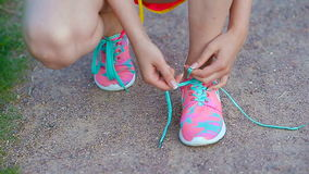 Hands of a young woman lacing bright pink and blue sneakers. Running shoes - closeup of woman tying shoe laces. stock video footage