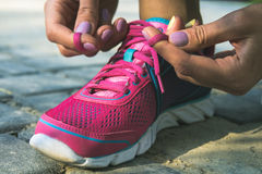 Hands of a young woman lacing sneakers. Hands of a young woman lacing bright pink and blue sneakers. Shoes standing on the pavement of stones and sand. In female Royalty Free Stock Image