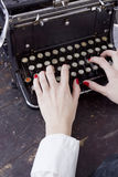 Hands of a young woman printed on a typewriter Stock Photo