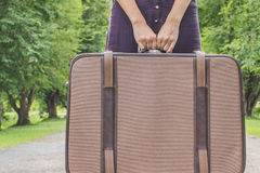 Hands of a young woman with a suitcase Stock Photos