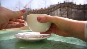 Hands of young woman taking a white cup of coffee or cappuccino from the table in restaurant outside stock footage