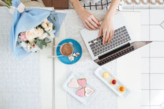 Hands of young woman using laptop at table in cafe Stock Photos