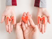 Hands of a younger daughter and her mother`s stock photos