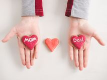 Hands of a younger daughter and word MOM stock photos