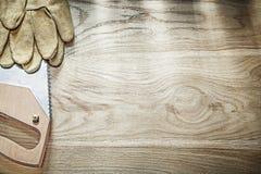 Handsaw afiado das luvas de couro da segurança no espaço c da cópia da placa de madeira foto de stock