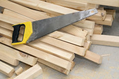 Handsaw on boards. Handsaw with yellow plastic handle on boards Stock Photo