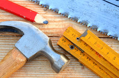 Handsaw, claw hammer, carpenter meter, pencil. Handsaw, claw hammer, carpenter meter and red pencil on wooden desk background Royalty Free Stock Photos