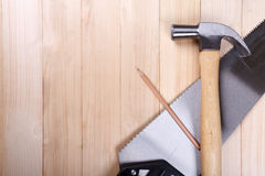 Handsaw, claw hammer and pencil on wooden desk background Royalty Free Stock Photo