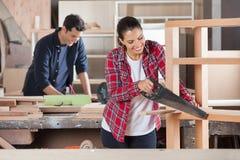 Handsaw de Cutting Wood With del carpintero en taller foto de archivo libre de regalías
