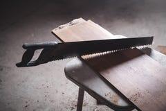 Handsaw met vloerplank stock foto