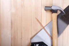 Handsaw, Tischlerhammer und Bleistift auf hölzernem Schreibtischhintergrund Lizenzfreies Stockfoto