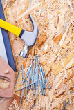 Handsawtischlerhammer und -nägel auf Sperrholz Stockbilder