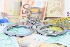 Handschellen auf dem Geld Stockbild