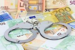 Handschellen auf dem Geld Lizenzfreie Stockfotos