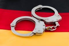 Handschellen auf deutscher Flagge Stockbild