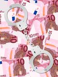 Handschellen auf Hintergrundvertikale des Euros zehn Stockfotografie