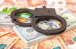 Handschellen, die auf einem Stapel von Dollarscheinen und Kreditkarte liegen Lizenzfreies Stockbild