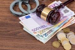 Handschellen mit Gesetzeshammer- und -Eurorechnungen, Münze auf Schreibtisch Lizenzfreies Stockbild